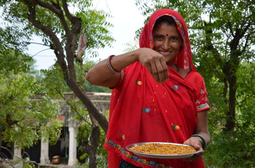 woman holding plate of grains