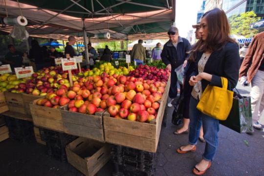 women choosing apples at farmers market